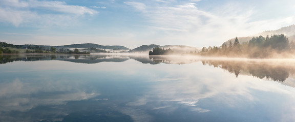 French landscape - Jura. View over the lake of Ilay in the Jura mountains (France) at sunrise with mist.