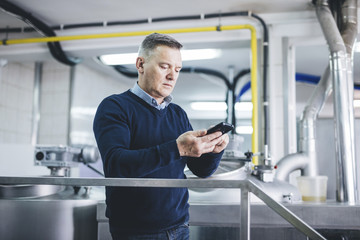 Brewer using smart phone while standing at brewery