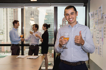 Youngs business people are celebrating success in office.