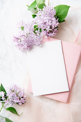 Top vew composition with feminine workspace mock up with empty card, lilac flowers and pink notebook on marble background