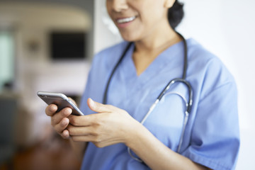 Midsection of female doctor using smart phone while working in hospital
