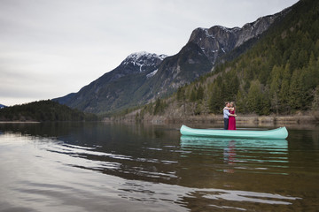 Young couple embracing while standing in canoe on lake against mountains