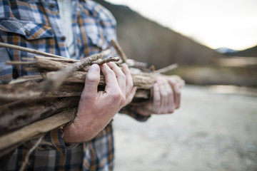 Midsection of man carrying firewood at Silver Lake Provincial Park