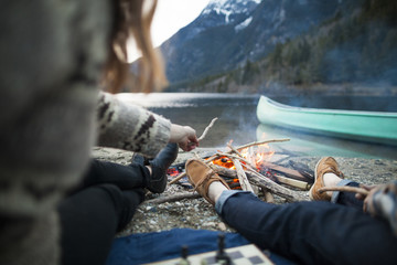 Low section of couple sitting by burning campfire at Silver Lake Provincial Park
