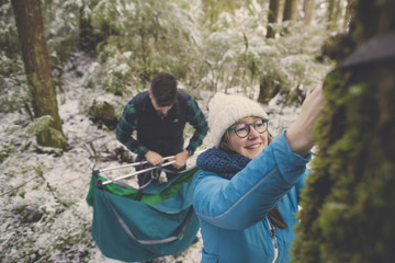 Smiling woman untying straps from tree trunk while man holding hammock in forest at Lynn Canyon Park during winter