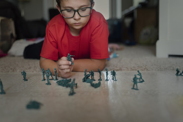 Boy playing with miniature plastic toy soldiers on floor at home