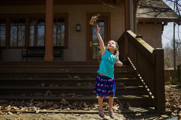 Playful girl jumping while throwing dry leaf in air against house during autumn