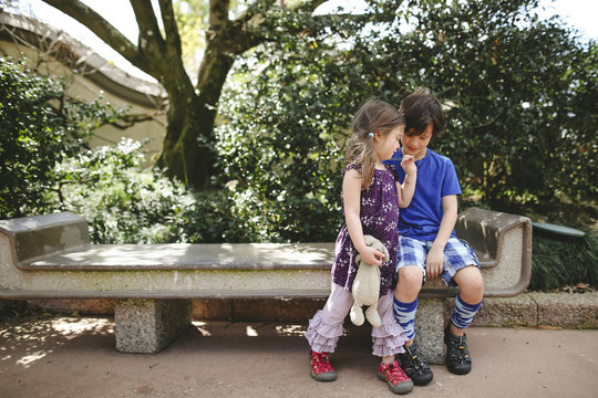Sister holding stuffed toy while brother sitting on bench at park