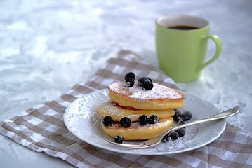 Pancakes with corn flour, sprinkled with powdered sugar and berries