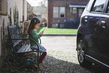 Side view of girl using mobile phone while sitting on bench at sidewalk by car
