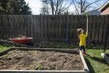 Girl playing with rake while gardening at backyard during autumn