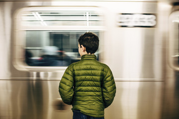 Rear view of boy wearing green jacket while standing at subway station