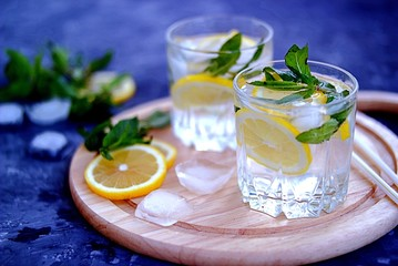 A cool drink, sparkling water with lemon , mint and ice in glasses on on a wooden board