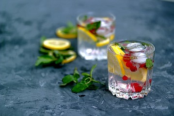 A cool drink, sparkling water with lemon, red currant, mint and ice in glasses on a dark gray concrete background