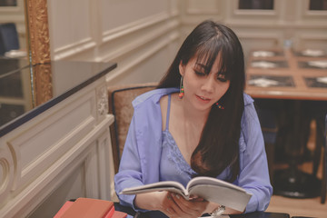 Education Concepts. Asian women are working in a restaurant. Asian women are reading a book in a restaurant.