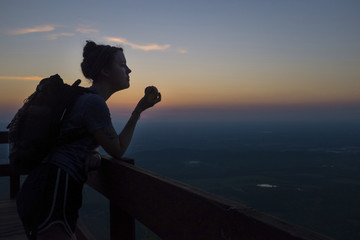 Female hiker eating apple while standing at observation point against sky during sunset
