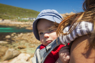 Midsection of mother carrying son in carriage while standing at beach against clear blue sky