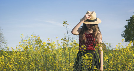 Teenage girl wearing hat while standing on field against blue sky during sunny day Wall mural
