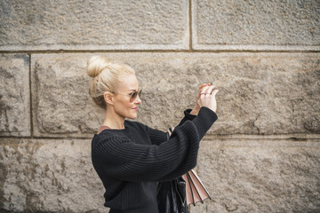 Side view of woman photographing while standing by wall