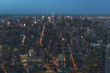 Aerial view of illuminated cityscape against clear sky at dusk