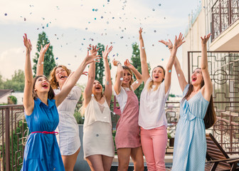 Girls Party. Beautiful Women Friends on the balcony Having Fun At Bachelorette Party. They are dancing in confetti with hands up