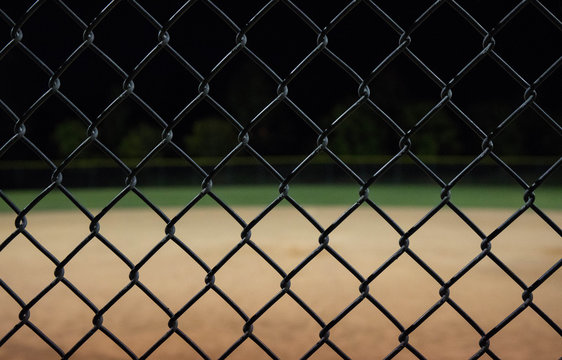 Close up photo of a baseball field fence looking through it to an empty field at night.  Great for background use.