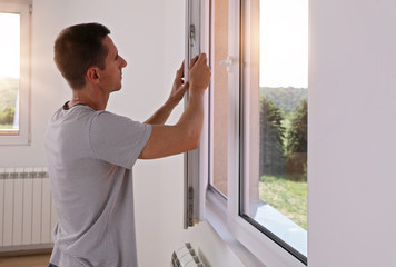 Man Installing New Windows In House