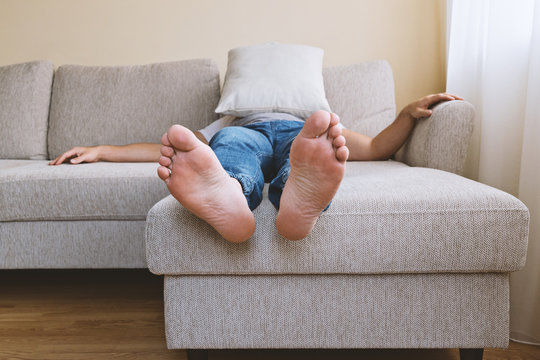 Faceless adult tired man in blue jogger jeans lying on beige sofa in depression. Men's depression concept