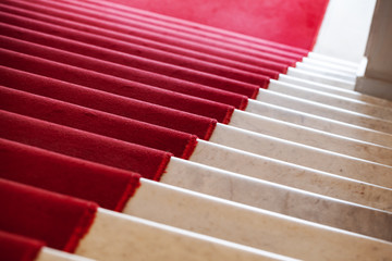 Red carpet lays on white marble stairs