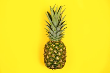 Pineapple on a bright bold yellow background. Minimal summer concept. Top view.