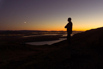 A man on a mountain stands overlooking Reykjavik at night in Iceland