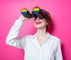 Beautiful redhead businesswoman with rainbow binoculars on pink background