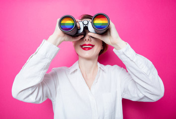 Beautiful red-haired businesswoman with binoculars on pink background