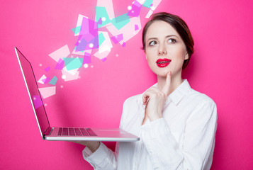 Portrait of young redhead businesswoman in white shirt with laptop and abstract windows on pink background