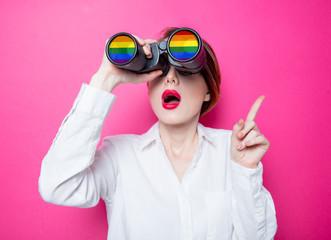 Beautiful redhead businesswoman with rainbow binoculars on pink background