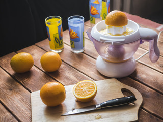 preparation of fresh orange juice smoothie with juicer on a wooden surface