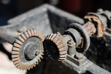 Old metal gears in drive mechanisms. Rusty gears used in machines from the last century.