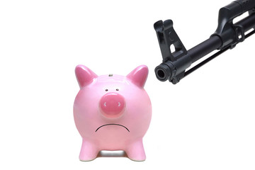A rifle pointing at a pink piggy bank / Terrorism threatening economy concept