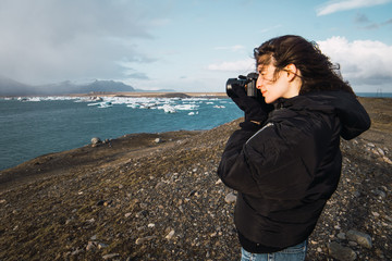 Woman taking photo of cold sea