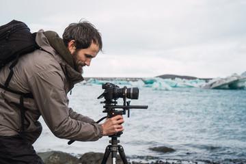 Man setting photographic equipment on coast