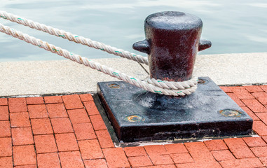 black iron ship's bollard with mooring lines on a red brick wharf at Baltimore's Inner Harbor