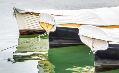 3 small sailboats covered with tarps moored in the water with reflections