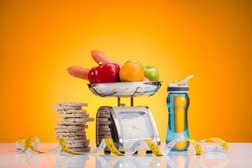 close-up view of fresh fruits and vegetables on scales, sports bottle with water and measuring tape on yellow