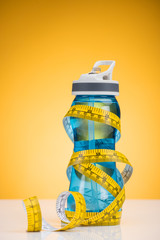close-up view of sports bottle with water and measuring tape on yellow