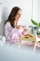 beautiful smiling woman in pink pajamas drinking coffee for breakfast in bed