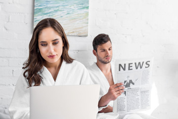 beautiful girlfriend using laptop while boyfriend reading newspaper in bed