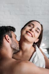 boyfriend kissing smiling girlfriends neck in bedroom in morning