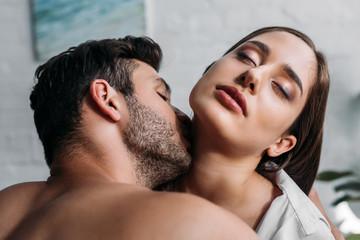boyfriend kissing sensual girlfriends neck in bedroom in morning