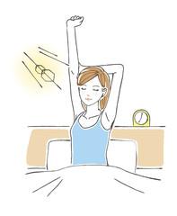 ベッドの上で背伸びをする女性 朝