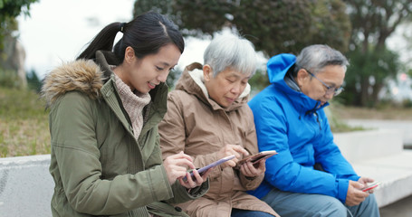 Asian Family using smart phone in the street